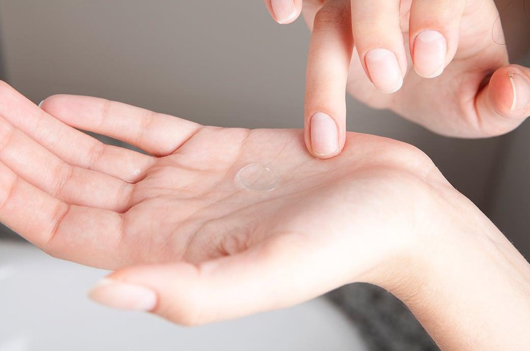 Uma mão mostrando uma lente de contato