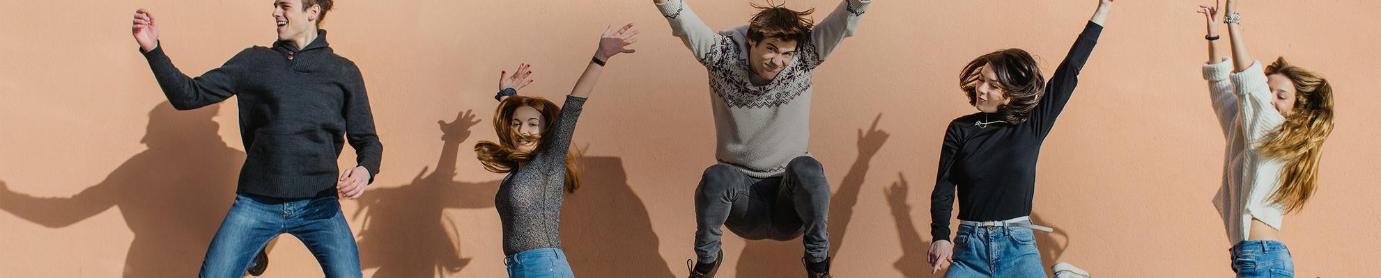 Um grupo de amigos pulando com os braços pra cima e sorrindo