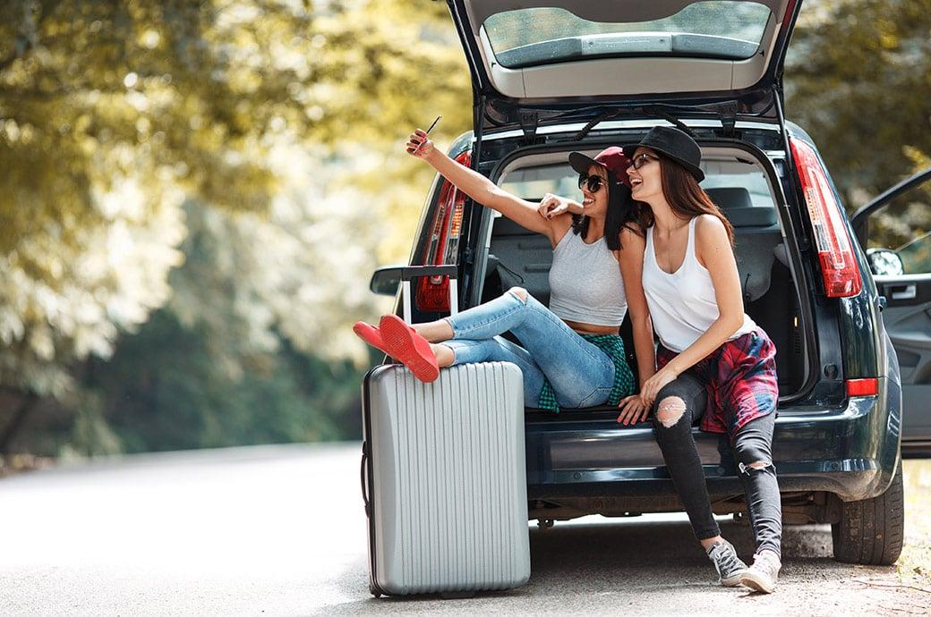 Duas garotas sentadas em um carro, tirando fotos e se preparando para ir viajar