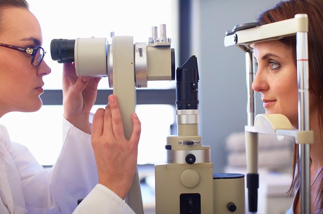 Uma imagem lateral de uma oftalmologista fazendo um exame de retina com sua paciente