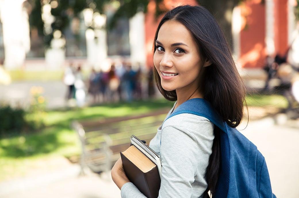 Uma garota sorrindo e carregando sua mochila e livros