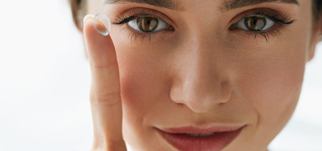 Uma mulher mostrando sua lente de contato